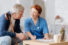 Reizende ausgebildete Krankenschwester, die Besonderen von ihr Arbeit erklärt stockbild