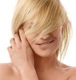 Reizende blonde Bissen ihre Lippe Stockfotografie