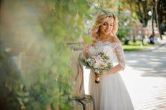 Reizende blonde Braut kleidete in einem schönen Kleid an Stockfotos