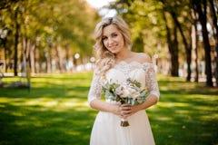 Reizende blonde Braut kleidete in einem schönen Kleid an, das auf dem Rasen steht Stockfotos