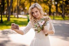 Reizende blonde Braut kleidete in einem schönen Kleid an, das Hochzeitsblumenstrauß hält und selfie macht Stockfotografie