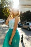 Reizende blonde Dame im Spitzekleid, das in der Sonne aufwirft, strahlt am stree aus Lizenzfreies Stockbild