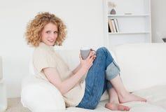 Reizende blonde Frau, die ein Cup genießt Stockfoto
