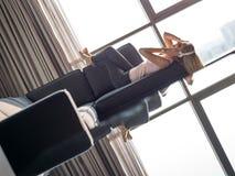 Reizende blonde Frau, die Musik beim Stillstehen auf Couch hört Lizenzfreie Stockfotografie