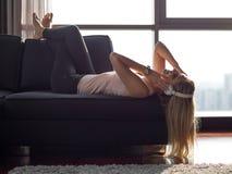 Reizende blonde Frau, die Musik beim Stillstehen auf Couch hört Stockfoto