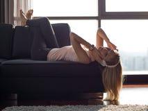 Reizende blonde Frau, die Musik beim Stillstehen auf Couch hört Lizenzfreies Stockfoto
