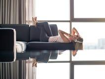 Reizende blonde Frau, die Musik beim Stillstehen auf Couch hört Lizenzfreies Stockbild