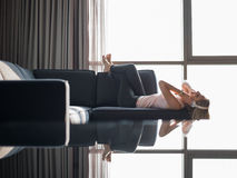 Reizende blonde Frau, die Musik beim Stillstehen auf Couch hört Lizenzfreie Stockfotos