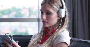 Reizende blonde Frau, die Musik beim Stillstehen auf Couch hört Stockbild