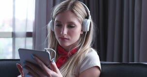 Reizende blonde Frau, die Musik beim Stillstehen auf Couch hört Stockfotos