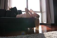 Reizende blonde Frau, die Musik beim Stillstehen auf Couch hört Lizenzfreie Stockbilder