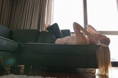 Reizende blonde Frau, die Musik beim Stillstehen auf Couch hört Stockbilder
