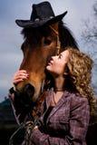 Reizende blonde Frau durch Pferd Stockfotos