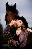 Reizende blonde Frau in einem bereitstehenden Pferd des Hutes Stockfotos