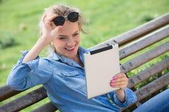 Reizende blonde Frau mit elektronischer Tablette in den Händen Stockbild