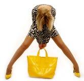 Reizende blonde Frau mit gelbem Beutel Stockbilder