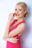 Reizende blonde lächelnde Frau bei der Aufstellung auf Weiß Stockbilder