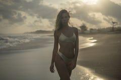 Reizende blonde Stellung in der schönen Haltung auf schwarzem Sandstrand, rosa untergehende Sonne stockfotos
