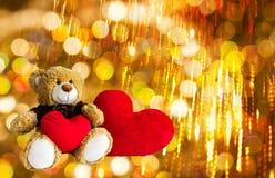 Reizende Braunbärgeschenkpuppe rote Herzen auf goldenem bokeh und FI Stockfotos