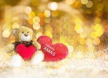 Reizende Braunbärgeschenkpuppe rote Herzen auf goldenem bokeh Weihnachten b Lizenzfreies Stockbild