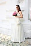 Reizende Braut mit Blumenstrauß von den Rosen Stockfoto