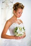 Reizende Braut mit Blumenstrauß der Blumen Stockbild