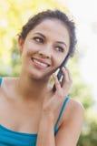 Reizende Brunettefrau, die mit ihrem Smartphone nennt stockbilder