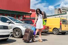Reizende conceptie, vrouw met koffer en auto royalty-vrije stock fotografie