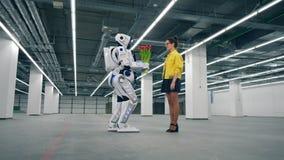 Reizende Dame nimmt Blumen von einem menschlich ähnlichen Roboter an stock video footage
