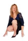 Reizende Frau, die auf Boden sich duckt Stockbild