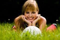 Reizende Frau, die auf einem Gras liegt Stockfotografie