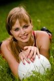 Reizende Frau, die auf einem Gras liegt Stockbilder