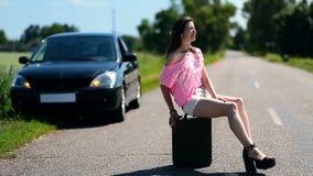 Reizende Frau, die auf Kanister auf Landstraße sitzt stock footage