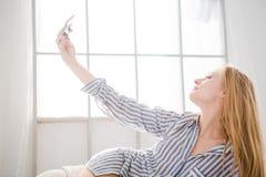 Reizende Frau, die Foto von unter Verwendung des Mobiltelefons liegt und macht Stockfoto
