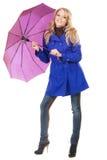 Reizende Frau in einem blauen Mantel mit Regenschirm Stockfotos