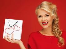 Reizende Frau im roten Kleid mit Einkaufstasche Lizenzfreies Stockbild