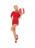 Reizende Frau im roten Kleid mit Geschenk Stockfotografie