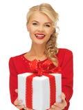 Reizende Frau im roten Kleid mit Geschenk Lizenzfreies Stockbild