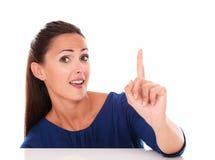 Reizende Frau mit dem Finger oben zeigend Stockfoto