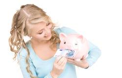 Reizende Frau mit piggy Querneigung und Geld Stockfotografie