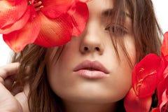Reizende Frau mit roten Blumen Stockbilder