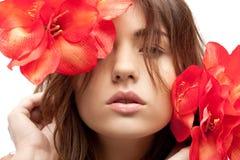 Reizende Frau mit roten Blumen Stockbild