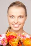 Reizende Frau mit roten Blumen Stockfoto