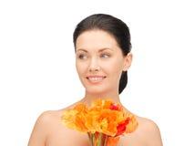 Reizende Frau mit roten Blumen Lizenzfreie Stockbilder