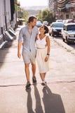 Reizende Frau und Mann, die im Sonnenlicht in Stadt geht Stockfoto
