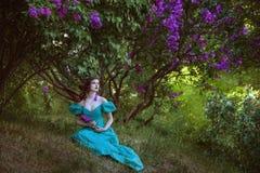 Reizende Frau unter einem Busch der Flieder lizenzfreie stockfotografie