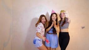 Reizende freundliche Mädchen feiern Geburtstag ihrer Freundinnen und haben den Spaß, der herein auf Hintergrund der hellen Wand s stock video footage