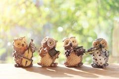Reizende glückliche Eulenpuppen, die eine Musik mit Sonnenschein spielen Musik conc Stockfoto