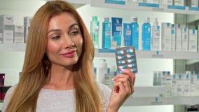 Reizende glückliche Frauenholdingblase von Pillen, lächelnd an der Apotheke stock footage