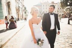 Reizende glückliche Hochzeitspaare, Braut mit dem langen weißen Kleid, das in der schönen Stadt aufwirft lizenzfreie stockfotos
